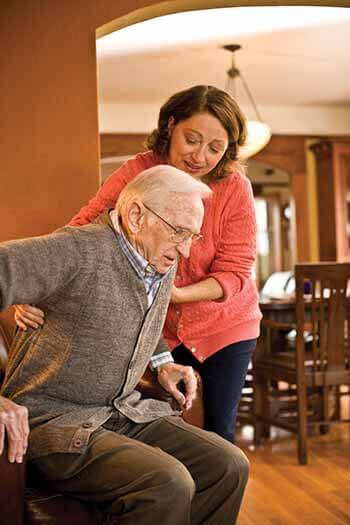 caregiver helping senior out of chair
